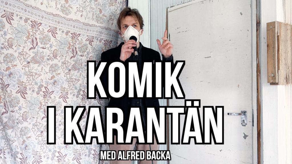 Komikern Alfred Backa står och talar i mikrofon med en ansiktsmask för munnen.